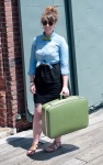 Female in bow tie, green suitcase